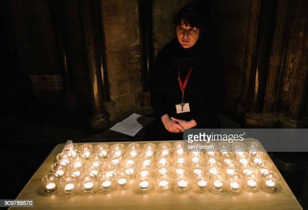 A member of staff sits next to a table full of candles as six hundred candles set out on the floor in the form of the Star of David are lit during a...