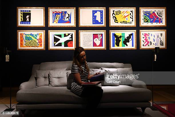 Member of staff sits on a couch near a collection of Henri Matisse original prints from his jazz portfolio at Christie's auction house on February...