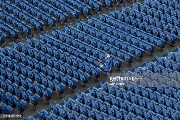 Member of staff sprays disinfectant onto seats at Yokohama Stadium to protect against Covid-19 coronavirus ahead of a baseball match between Yokohama...