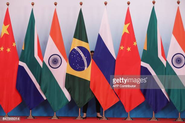 A member of staff stands behind national flags of Brazil Russia China South Africa and India to tidy the flags ahead a group photo during the BRICS...