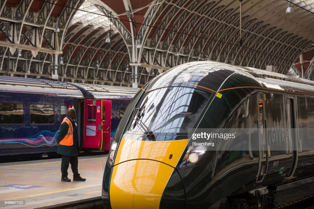 A member of staff stands next to a Great Western Railway train service, operated by FirstGroup Plc, at London Paddington railway station in London, U.K., on Monday, April 16, 2018. British train and bus operator FirstGroup Plc said it rejected an 'opportunistic' takeover proposal that private-equity firm Apollo Management made as the company struggles with under-performing rail routes in the U.K. and competition from discount airlines in the U.S. Photographer: Jason Alden/Bloomberg via Getty Images