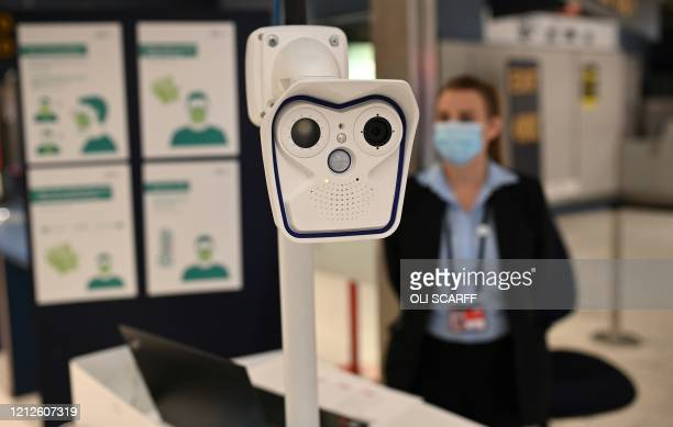 A member of staff stands with a body temperature screening device being trialled during the COVID19 pandemic at the entrance to passport control...