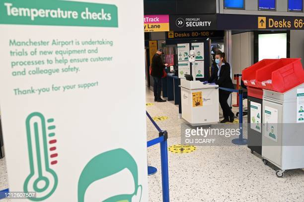 Member of staff stands with a body temperature screening device, being trialled during the COVID-19 pandemic, at the entrance to passport control...