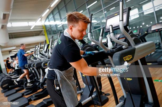 Member of staff uses anti-bacterial wipes to clean an exercise machine at Nuffield Health Sunbury Fitness and Wellbeing Gym in Sunbury-on-Thames,...