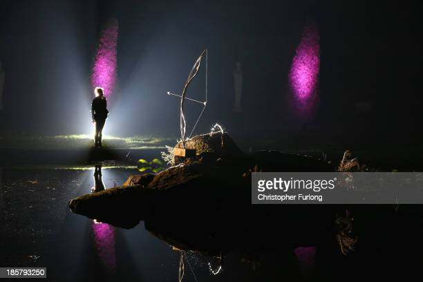 Member of staff views the illuminated Ring Pond in the gounds of Chatsworth stately home as it is lit up as part of the Luminaire event at Chatsworth...
