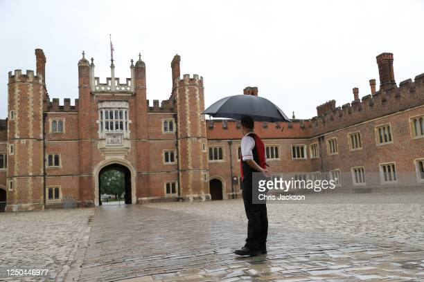 Member of staff waits for the public to arrive for the reopening of the Tudor gardens at Hampton Court Palace on June 18, 2020 in London, England. In...