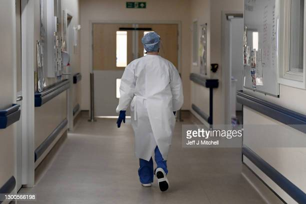 Member of staff walks in the ICU ward corridor at University Hospital Monklands on February 5, 2021 in Airdrie, Scotland. The numbers of patients...