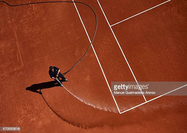 A member of staff waters down the court during day two of the Barcelona Open Bac Sabadell at the Real Club de Tenis Barcelona on April 21 2015 in...