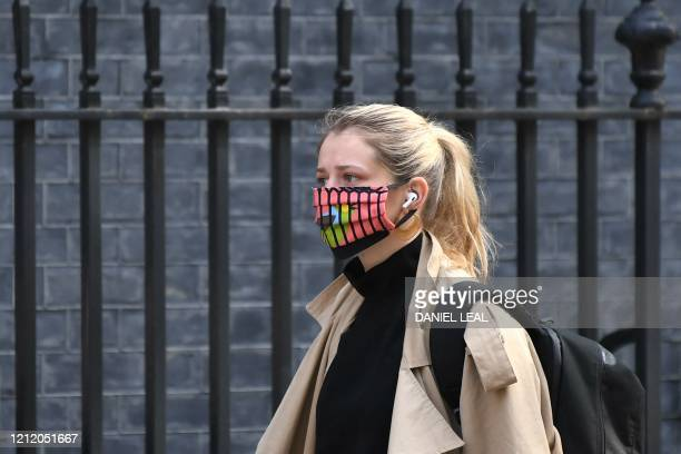 A member of staff wearing a colourful mask arrives in Downing Street in central London on May 7 2020 The British government was on May 7 reviewing...