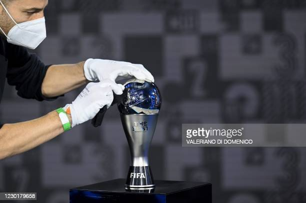 Member of staff wearing a face mask and gloves cleans a Best FIFA trophy ahead of The Best FIFA Football Awards 2020 ceremony, at the FIFA...