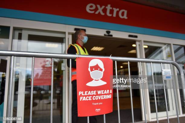 Member of staff wearing a face mask monitors the entrance to an Argos store which displays a public health notice reminding customers to wear a face...