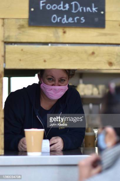A member of staff wearing a face mask serves a customer with a take away coffee from a food and drink kiosk on Westcliff seafront on October 30 2020...