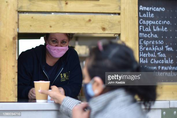 Member of staff wearing a face mask serves a customer with a take away coffee from a food and drink kiosk on Westcliff seafront on October 30, 2020...