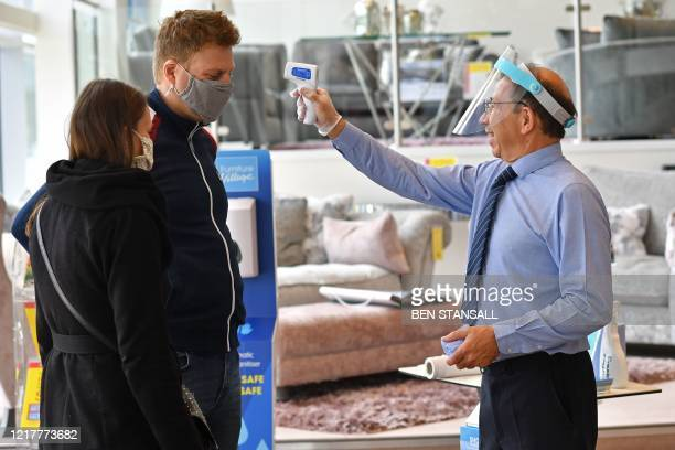 Member of staff wearing a face shield uses a laser thermometer to test a customer's temperature in a Furniture Village store in Croydon, in...