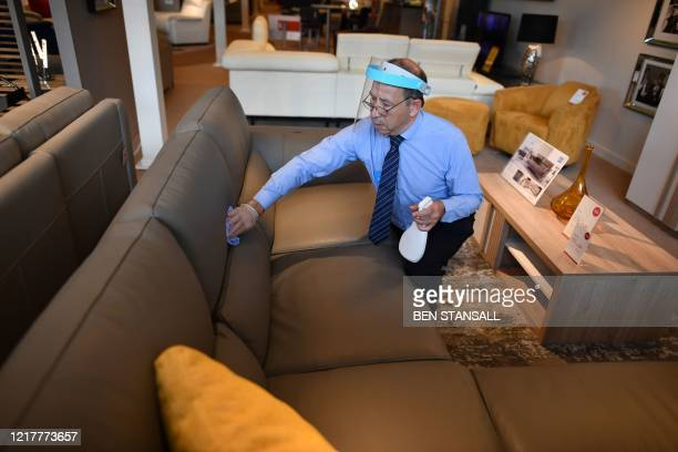 Member of staff wearing a face shield uses disinfectant to clean a sofa in a Furniture Village store in Croydon, in south-east London on June 5...