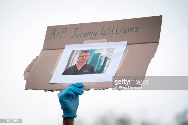A member of staff wearing a face visor holds up a sign which says 'RIP Jeremy Williams' as people clap at the Royal Gwent Hospital on April 16 2020...