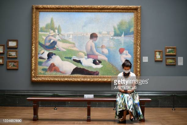 """Member of staff wearing a protective face covering poses in front of """"Bathers at Asnieres"""" by Georges Seurat inside the National Gallery on July 4 as..."""