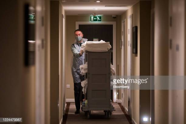 A member of staff wearing a protective face mask at the Holiday Inn Whitechapel hotel operated by InterContinental Hotels Group Plc pushes a trolley...