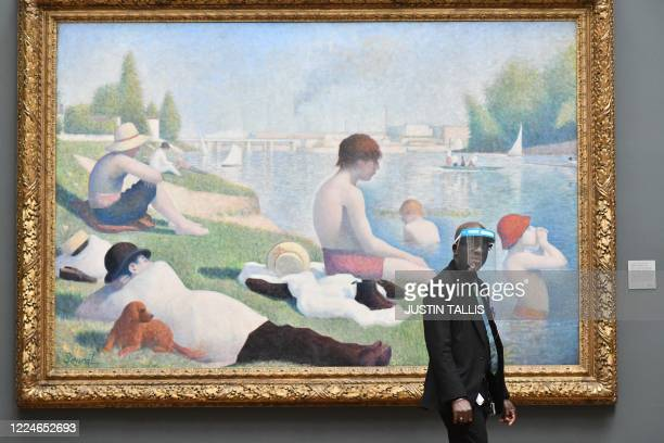 """Member of staff wearing a protective face shield walks past """"Bathers at Asnieres"""" by Georges Seurat inside the National Gallery on July 4 as the..."""