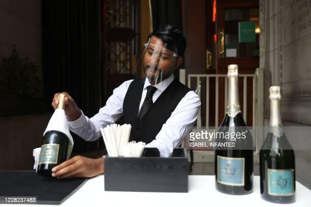 Member of staff wearing a visor as a precaution against the spread of the novel coronavirus prepares bottles of wine inside restaurant 1 Lombard...