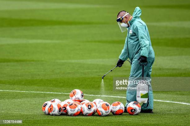 Member of staff wearing personal protective equipment disinfecting equipment during a training session at Melwood Training Ground on May 24 2020 in...