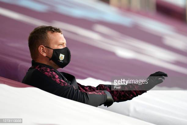 A member of staff wearing personal protective equipment looks on during the Carabao Cup second round match between Burnley and Sheffield United at...