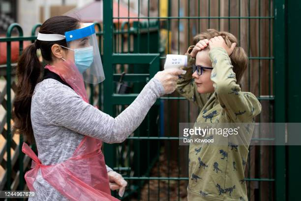 A member of staff wearing personal protective equipment takes a child's temperature at the Harris Academy's Shortland's school on June 04 2020 in...