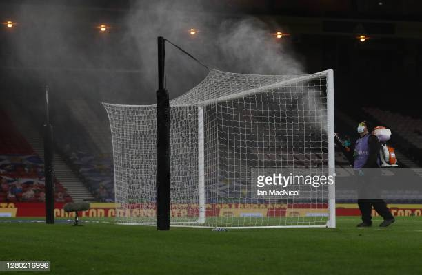 A member of staff wearing PPE disinfects the goal at half time during the UEFA Nations League group stage match between Scotland and Czech Republic...