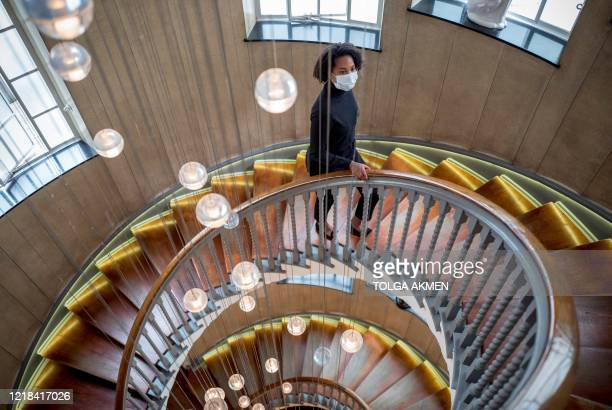 Member of staff wearing PPE , including a face mask as a precautionary measure against COVID-19, walks up the Cecil Brewer staircase at the re-opened...