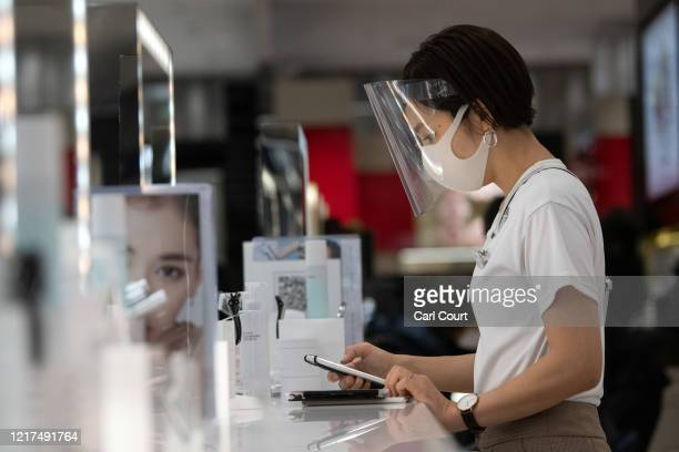 Member of staff wears a face mask and a plastic visor as she works in a cosmetics shop at Isetan department store in Shinjuku on June 4, 2020 in...