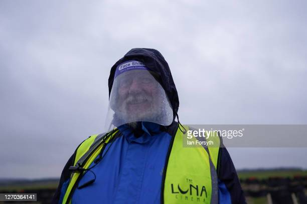 Member of staff wears a face shield as families attend a screening of The Greatest Showman during the Luna Cinema movie experience at Castle Howard...