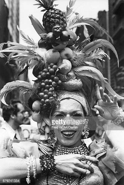 A member of STAR the Street Transvestites Action Revolutionaries poses in an elaborate costume and headdress covered in fruit and feathers at fourth...