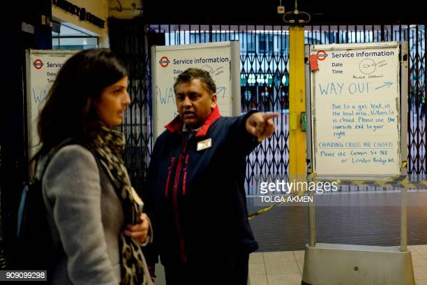 A member of station staff directs a passenger up at Embankment tube station where notice boards are set up advising passengers of a gas leak closing...