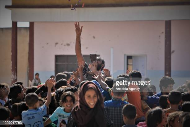 A member of Syrian National Army gives gifts to kids before an event to mark the first year of Operation Peace Spring as life turned to normal in Tal...