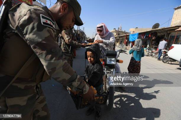 A member of Syrian National Army offers candy to kids during an event to mark the first year of Operation Peace Spring as life turned to normal in...