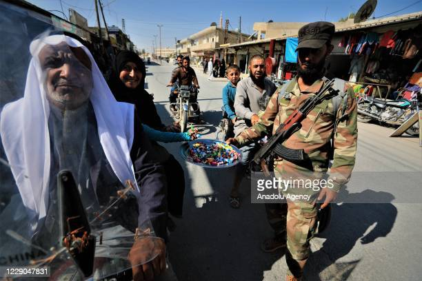 A member of Syrian National Army offers candy to people during an event to mark the first year of Operation Peace Spring as life turned to normal in...