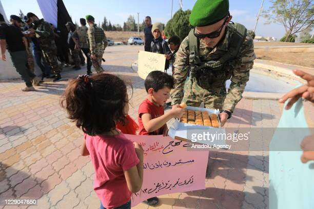 A member of Syrian National Army offers dessert to kids during an event to mark the first year of Operation Peace Spring as life turned to normal in...