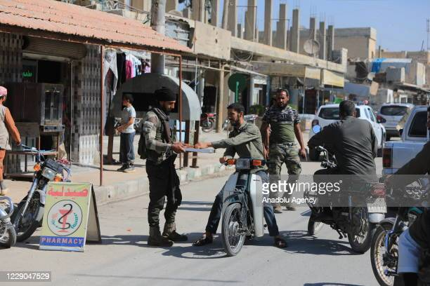 A member of Syrian National Army offers dessert to people during an event to mark the first year of Operation Peace Spring as life turned to normal...