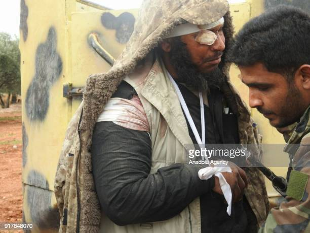 A member of Syrian opponents body searches a wounded Daesh militant as Daesh militants get off from the truck in Idlib Syria on February 13 2018...