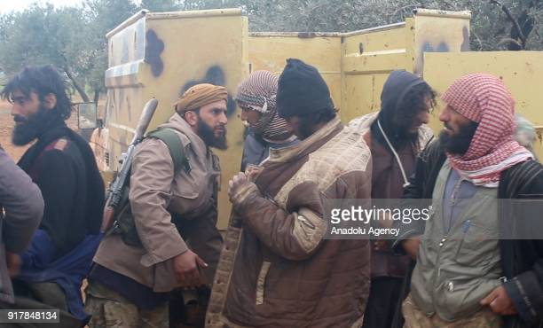 A member of Syrian opponents body searches the Daesh militants as Daesh militants get off after they were captured in Idlib Syria on February 13 2018...