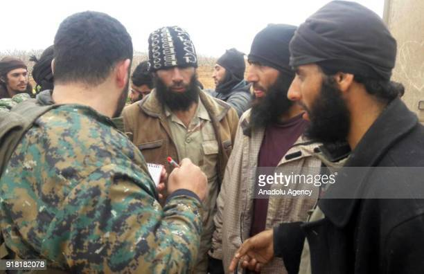 A member of Syrian opponents interrogates Daesh militants who tried to infiltrate Idlib deescalation zone via Assad Regime's corridor after they were...