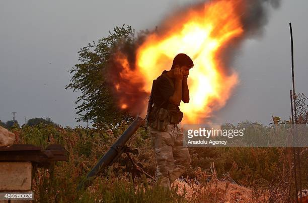 A member of Syrian opposition group linked to Damascus Front covers his ears as he fires a rocket towards Daesh terrorist in Harbal village north of...