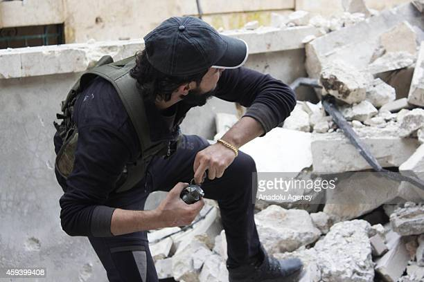 A member of Syrian opposition takes position to throw hand grenade to the Assad Regime Forces in northern Aleppo city of Syria on November 21 2014