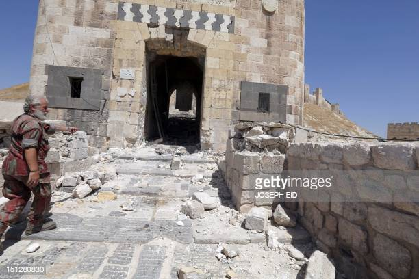 A member of Syria's government forces gestures near the partially destroyed entrance of Aleppo's historical citadel on September 4 2012 Syrian troops...