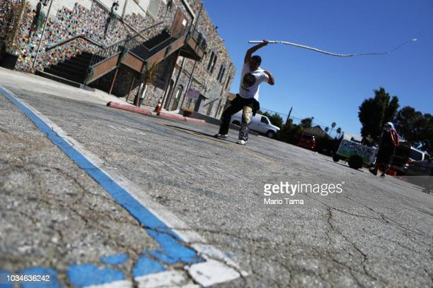 A member of Tecuanes Los Angeles snaps a large whip creating a sound effect near the 72nd annual East LA Mexican Independence Day Parade on September...