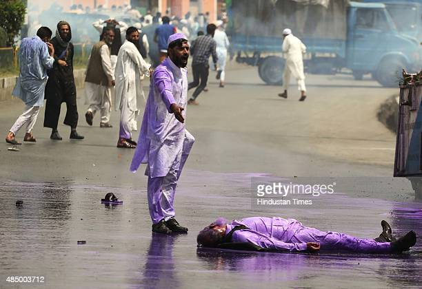 A member of TehreekeHurriyat laying on ground as other shout pro freedom slogans while police spray purple coloured water cannon to disperse a...