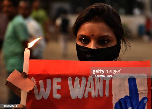 Member of Thalassaemia and AIDS Prevention Society holds a placard during a silent candle protest against the recent Hyderabad gang-rape, at Baje...