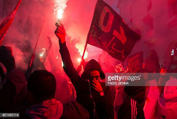 A member of the 20 February Movement carries a flare during a demonstration on November 6 2016 in the capital Rabat to demand justice for a fish...