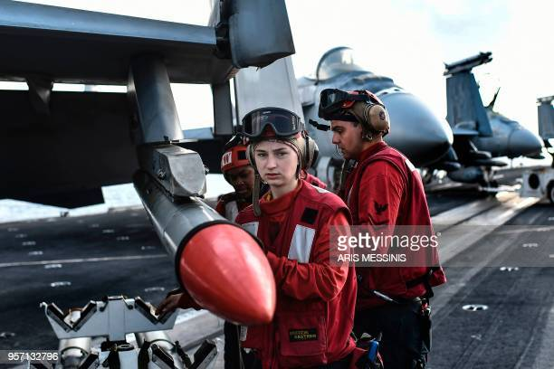 A member of the 330 meters aircraft US carrier Harry S Truman looks on after placing a missile on an F18 fighting jet on eastern Mediterranean Sea on...