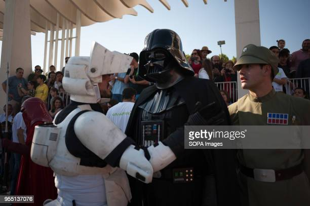 A member of the 501st Legion Spanish Garrison dressed as 'Darth Vader' from the movie saga Star Wars talks with a stormtrooper as they perform during...